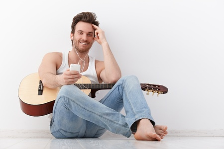 man playing guitar: Happy young guitarist sitting on floor with guitar, using mp3 player. Stock Photo