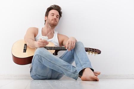 guitarra sexy: Apuesto joven guitarrista escuchar m�sica a trav�s de los ojos de auriculares cerrados.