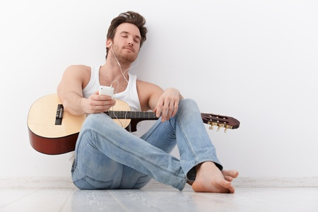 Handsome young guitarist listening to music through headphones eyes closed. photo