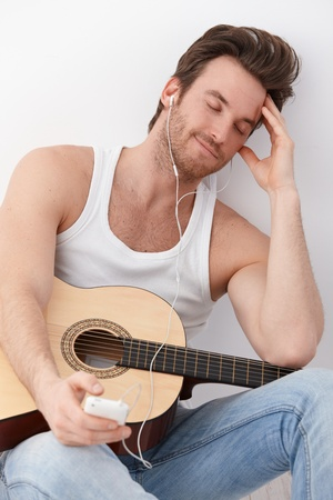 Sexy guitar player sitting on floor, listening to music through headphones, having mp3 player, smiling. photo