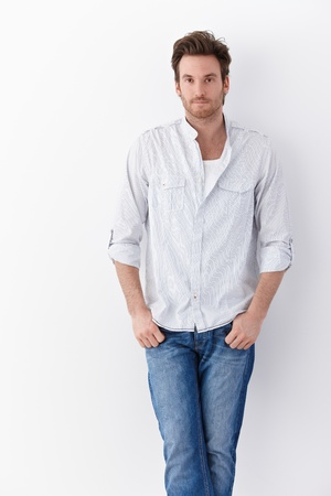 Handsome young man standing over white background, wearing shirt and jeans. photo