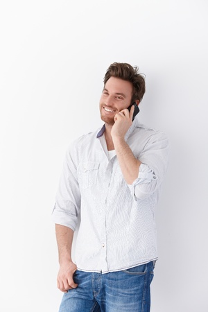 Happy young man using mobile phone, standing over white background, smiling. photo