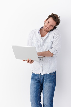 Busy young man using mobile and laptop, smiling. Imagens