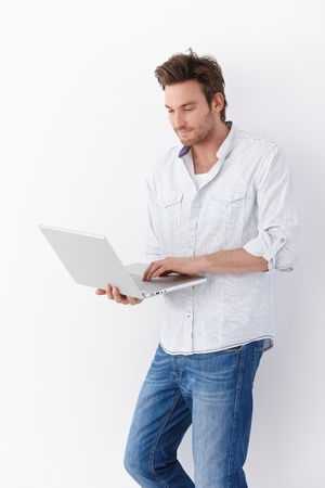 1 man only: Casual young man using laptop, standing by wall.