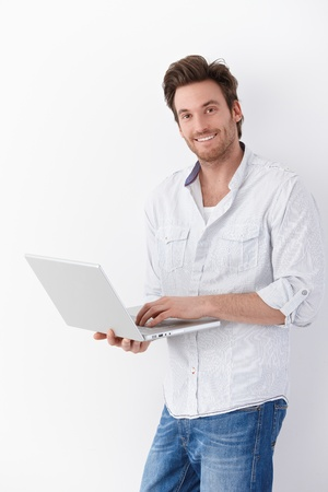 stubbly: Handsome young man browsing internet on laptop, smiling.