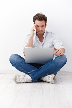 Young man sitting in tailor seat, browsing internet on floor. photo