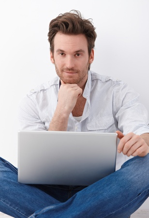 Handsome young man sitting in tailor seat on floor, using laptop, smiling. photo