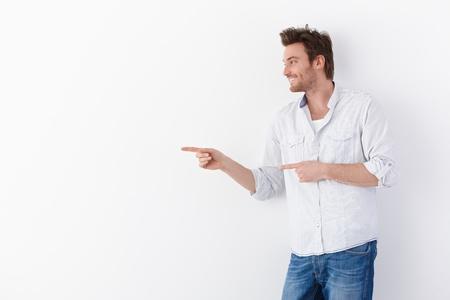 finger pointing: Joven permanente sobre fondo blanco, apuntando a la derecha, sonriendo.