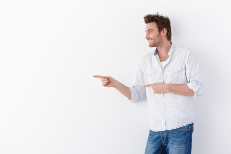 Young man standing over white background, pointing to right, smiling. Stock Photo - 9434798