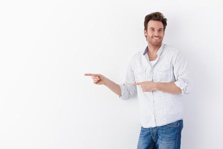 young man standing: Felice giovane uomo in piedi su sfondo bianco, che punta a destra, sorridendo a fotocamera. Archivio Fotografico