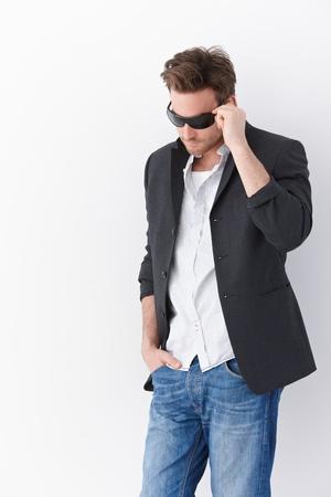 homem: Stylish man wearing sunglasses, standing over white background.
