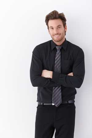 Happy young businessman standing arms crossed over white background. photo