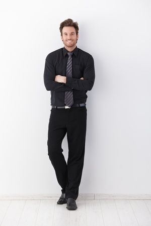 stubbly: Confident young businessman smiling arms crossed, leaning to wall.
