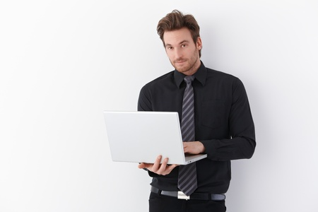 Handsome young businessman standing over white background, holding laptop, smiling. photo