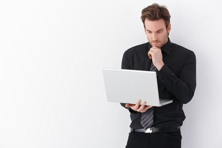 stubbly: Handsome young businessman working on laptop, standing over white background. Stock Photo