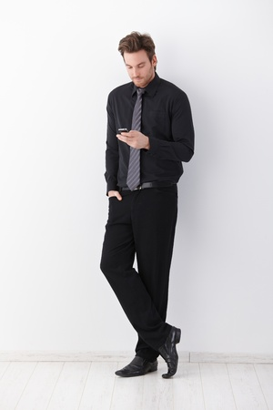 Stylish businessman standing over white background, writing text message.
