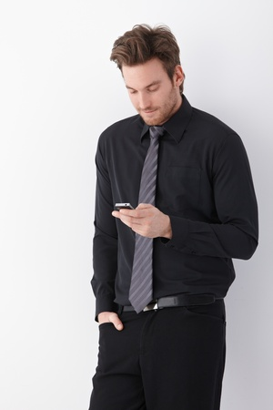 Young handsome businessman using mobile phone. photo