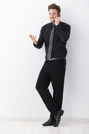 Young businessman in black talking on mobile phone, gesturing, smiling. photo