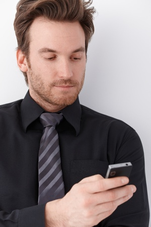 Portrait of handsome young businessman using mobile phone. Stock Photo - 9435327