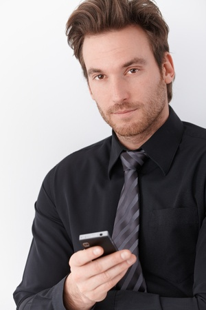 Goodlooking young businessman holding mobile phone. photo