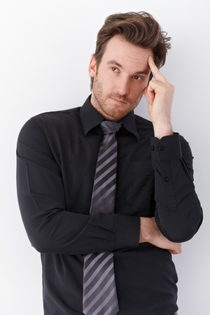 offish: Young businessman standing over white background, thinking.