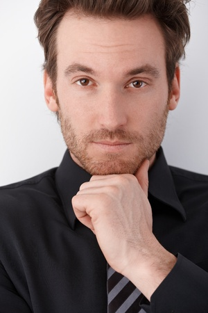 Closeup portrait of handsome young businessman looking at camera. photo
