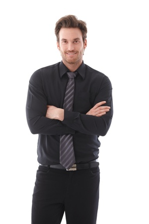 Confident young businessman standing arms crossed, smiling.