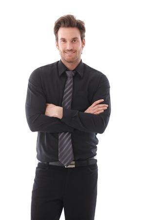Vertrouwen jonge zakenman staande wapens gekruist, glimlachend. Stockfoto