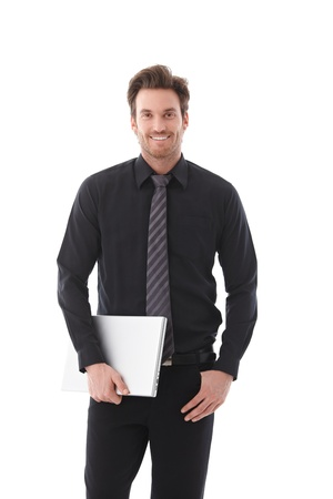 happily: Handsome young businessman holding laptop, smiling happily. Stock Photo