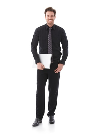 Confident businessman holding laptop, smiling. Stock Photo - 9434556