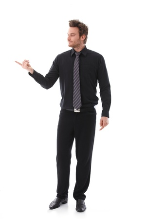Young businessman balancing an invisible object on his forefinger. Stock Photo - 9434559