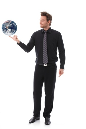 Young businessman balancing a globe on his forefinger. Stock Photo - 9434567