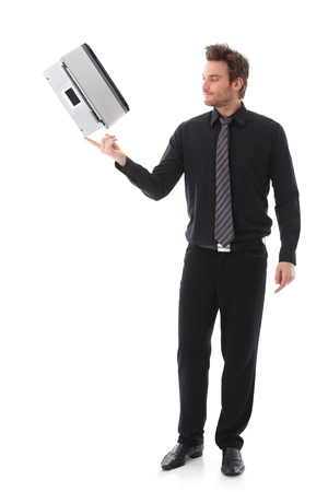 Young businessman balancing a laptop on his forefinger. Stock Photo - 9434563