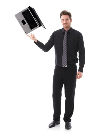 Young businessman balancing a laptop on his forefinger, looking at camera. Stock Photo - 9434574
