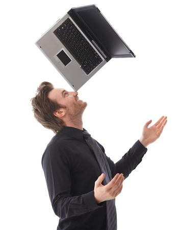 Happy young man balancing a laptop on his nose, smiling. Stock Photo - 9434674