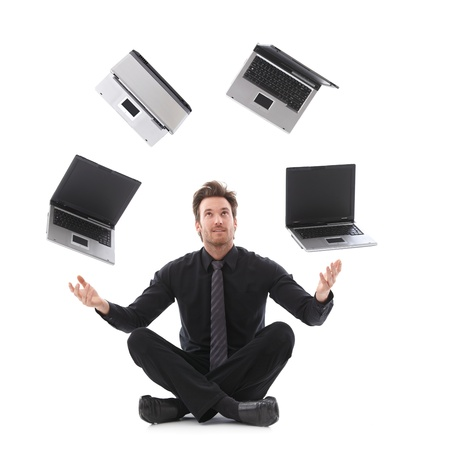 arms open: Handsome businessman in tailor seat juggling with laptops.