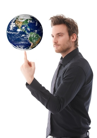 Goodlooking young businessman balancing a globe on his forefinger, concentrating. photo