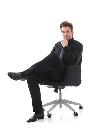 hombre sentado: Seguro de empresario guapo sentado en silla, sonriendo.