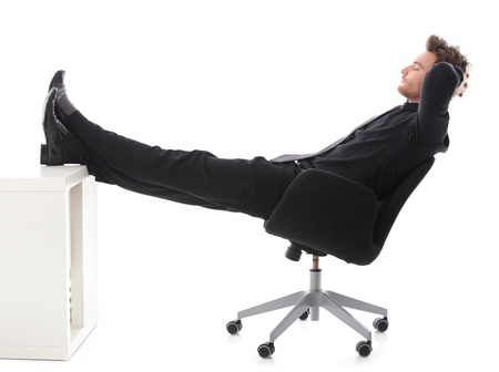 Young businessman sitting on chair, resting with legs on desk, eyes closed. photo