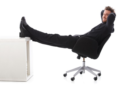 Young businessman taking a break, resting with legs on desk, smiling. Stock Photo - 9434660