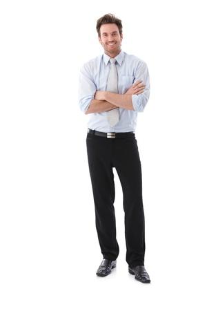 hombre de negocios: Armas de permanente de empresario confía cruzaron, sonriendo. Foto de archivo