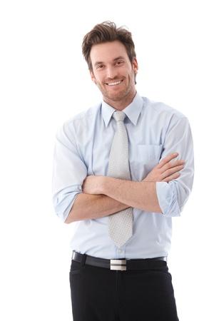 Knappe jonge zakenman staande wapens gekruist, glimlachend vol vertrouwen. Stockfoto