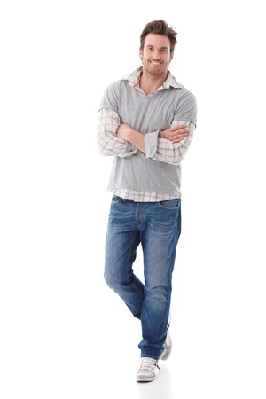 image size: Confident young man wearing jeans and shirt standing arms crossed, smiling.