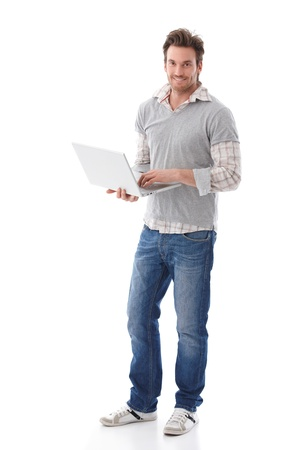 young man standing: Casual young man holding laptop in hands, smiling. Stock Photo