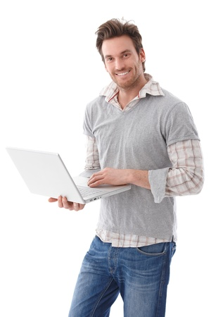 Happy young man using laptop, standing, smiling. Stock Photo - 9434797