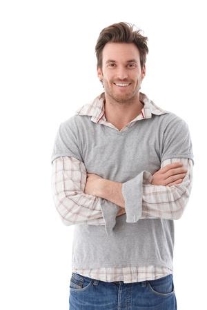 mani incrociate: Fiducioso giovane guardando fotocamera braccia incrociate, sorridente.