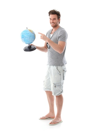 Handsome young man planning holiday, holding globe, smiling. photo