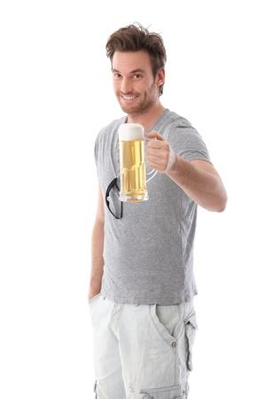 single beer bottle: Handsome young man drinking beer, smiling.