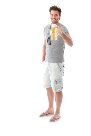 single beer bottle: Happy young man drinking beer, holding beer mug, smiling. Stock Photo
