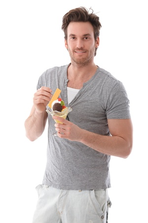 over eating: Handsome young man holding ice cream cup smiling. Stock Photo